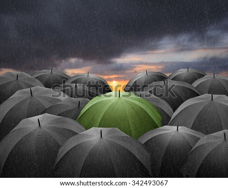 Outstanding Green umbrella among many dark crowd / umbrellas.  - stock photo