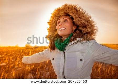 outstretched arms female in sunrise landscape - stock photo