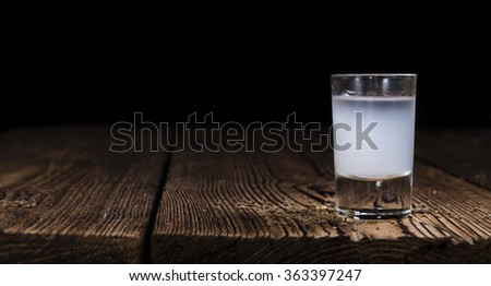 Ouzo (Greek aperitif) in a shot glass on wooden background (selective focus) - stock photo