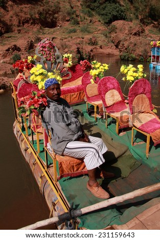 OUZOUD, MOROCCO - JUNE 01: A boatman waits for excursion passengers in his colourful home made raft at the Ouzoud waterfalls, a popular tourist destination. On June 01, 2012 in Ouzoud, Morocco.  - stock photo