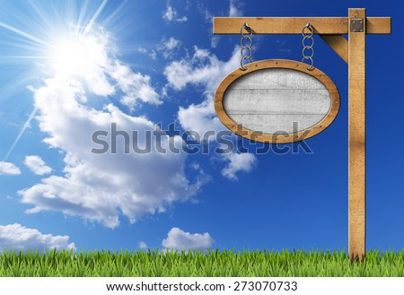 Oval Sign with Frame Chain and Pole. Empty oval wooden sign with wooden brown frame hanging with metal chain on a wooden pole, on blue sky with clouds, sun rays and green grass - stock photo
