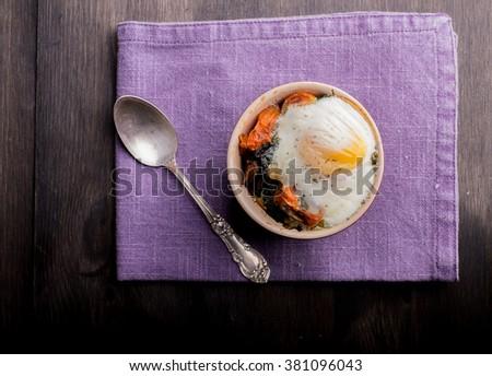Oven baked breakfast egg on salad - stock photo