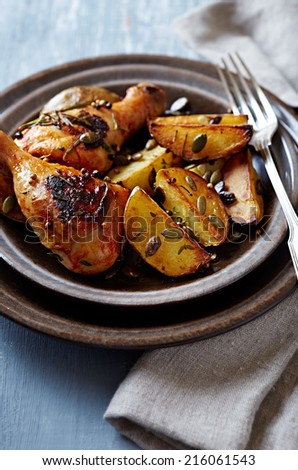 Oven-baked chicken and potatoes with pumpkin seeds   - stock photo