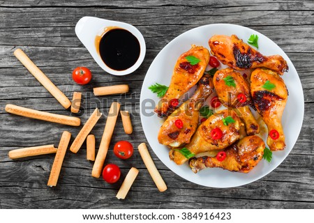 Oven baked golden sticky chicken drumsticks marinated with honey, soy sauce and ginger on a white dish with pieces of chili pepper and parsley, Asian flavors and style, top view - stock photo