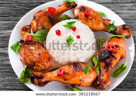Oven baked golden sticky chicken drumsticks marinated with honey, soy sauce and ginger on a white dish with rice, pieces of chili pepper, spinach, chard and parsley, Asian flavors and style, close-up - stock photo