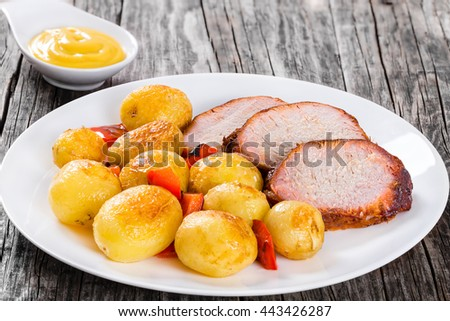 Oven Baked new potatoes with sea salt, red bell pepper and pork tenderloin cutting into slices on a white dish with sauce in a gravy boat on a wooden background, close-up, view from above - stock photo