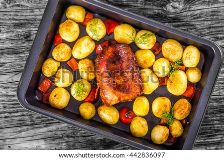 Oven Baked new potatoes with sea salt, red bell pepper and pork tenderloin in a baking dish, on a wooden table, close-up, view from above - stock photo