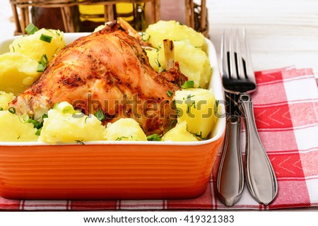 Oven baked rabbit with potatoes  in orange ceramic bowl on white  wooden table. - stock photo