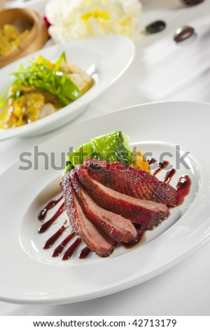Oven crisp duck breast marinated in a Peking duck style sauce on a tian of polenta and sweet potato, honey bok choy and julienne cucumber - stock photo