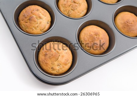 Oven fresh oatmeal and raisin muffins in baking tray - stock photo