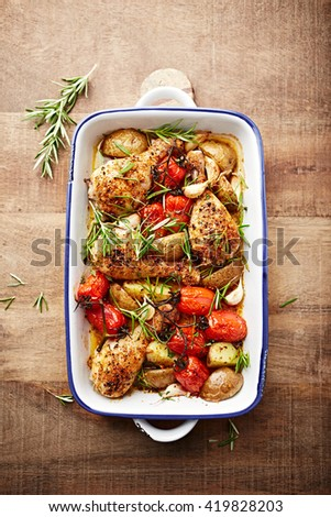 Oven-roasted, chicken with cherry tomatoes, potatoes and garlic - stock photo