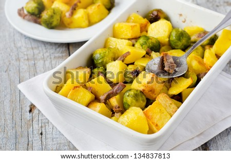 Oven roasted potatoes and Brussels sprouts with bacon - stock photo