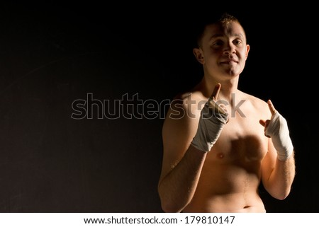 Over confident young boxer gesturing with his fingers before his match to show his confidence and disdain for his opponent, on black with copyspace - stock photo