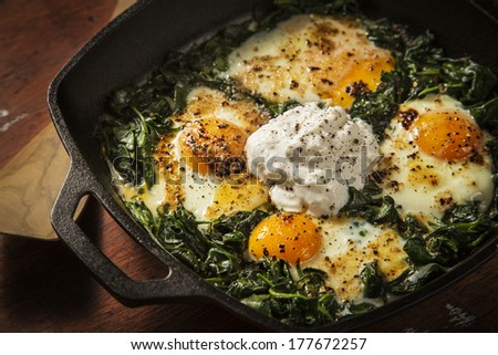 Over easy eggs with Spinach and Garlic in a Cast Iron Skillet on a Wooden Table With a Spatula - stock photo