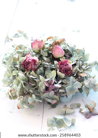 Over exposed, pale image of dried blue hydrangea and pink rose buds, a romantic, ethereal flower arrangement on white wooden floorboards, wedding bouquet in pastel colors  shabby chic - stock photo