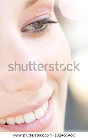 Over head close up beauty portrait of a young caucasian healthy woman face and eye looking down with long eyelashes and sparkling lights in the background. - stock photo