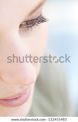 Over head close up beauty portrait of a young caucasian healthy woman face and eye looking down with long eyelashes. - stock photo