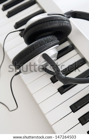 Over head close up detail view of an electric keyboard and music head phones together on a white desk. - stock photo