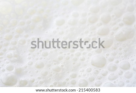 Over head close up full frame background detail view of frothy white milk creating bubbles, indoors. Macro still life view of liquid milk drink. - stock photo