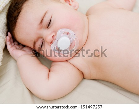 Over head close up portrait of a baby girl sleeping on a bed at home and sucking a white dummy, dreaming. - stock photo