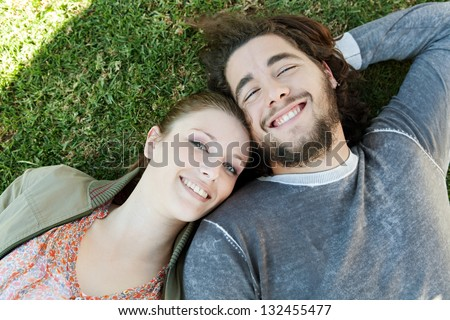 Over head close up portrait of a young bohemian couple laying down on green grass with their heads together in a sunny park, smiling. - stock photo
