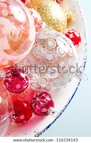Over head detail view of a bunch of different size and design christmas balls in a silvery dish against a blue background. - stock photo