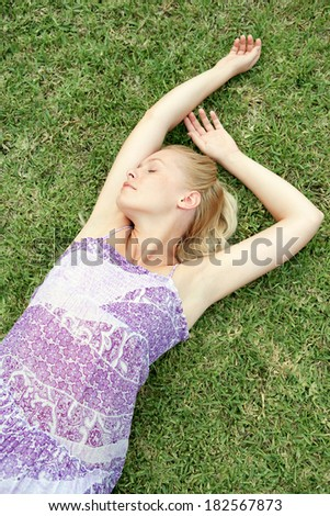 Over head portrait of a beautiful blond young woman laying down and relaxing on healthy green grass with her eyes shut, enjoying a summer day in nature. Health and beauty lifestyle. - stock photo