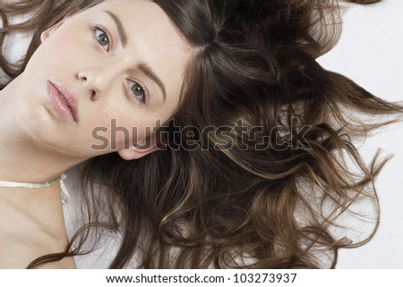 Over head portrait of a young woman laying down with her hair spread around her. - stock photo