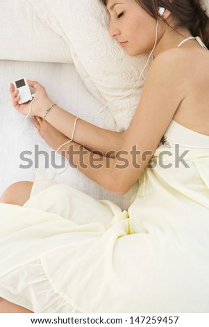 Over head view of a beautiful young woman laying down on an outdoors bed while on vacation and listening to music with her headphones, relaxing with her eyes closed, close up. - stock photo