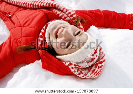 Over head view of a beautiful young woman laying down on the snow moving her arms up and down creating a snow angel figure, playing games while on a sunny winter vacation. - stock photo