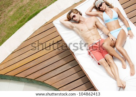 Over head view of a young, attractive couple sunbathing by a swimming pool while on holiday. - stock photo