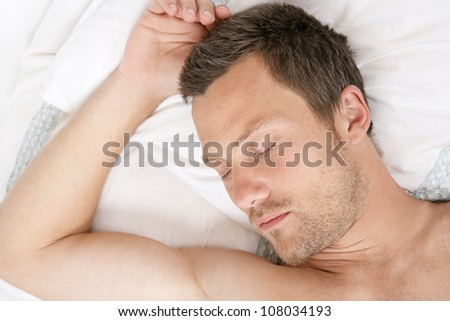 Over head view of a young man sleeping in bed. - stock photo