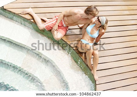 Over head view of an attractive couple sunbathing and being affectionate while sitting by a swimming pool's steps in a hotel's garden. - stock photo