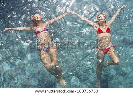 Over head view of two young women wearing bikinis and floating in water while holding hands, full frame. - stock photo