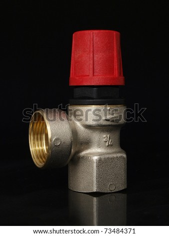 over pressure release valve on black ground - stock photo