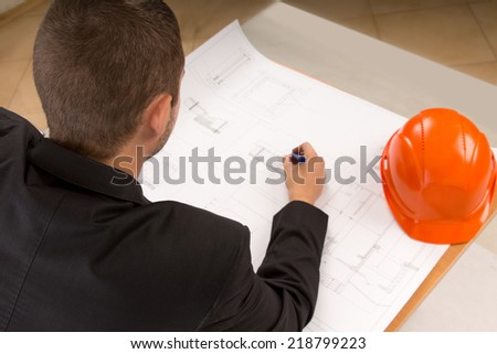 Over the shoulder view of a young architect with a pencil in his hand modifying a building plan as he sits at a table with his hardhat alongside - stock photo
