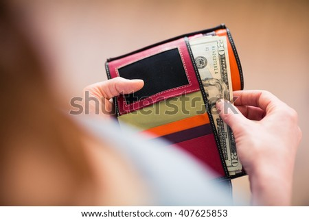 Over the shoulder view of a young woman taking US Dollar bills out of her wallet. Shallow DOF. - stock photo