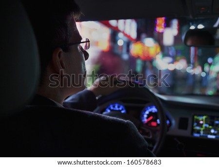 Over the shoulder view of businessman driving at night in city - stock photo
