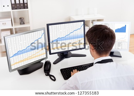 Over the shoulder view of the computer screens of a stock broker trading in a bull market showing ascending graphs - stock photo