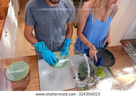 Over view of couple doing household chores in the kitchen - stock photo
