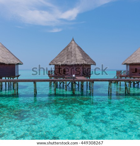 Over water  bungalows with stair descending into the sea. Turquoise color of the lagoon. Tropical island in the Indian Ocean. Luxury holiday. - stock photo