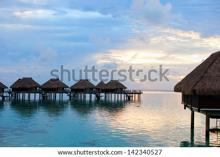 Over water villas at sunset in French Polynesia - stock photo
