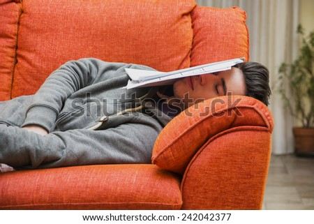 Over-worked, tired young man at home sleeping instead of working or studying, resting with head covered by paper sheets - stock photo