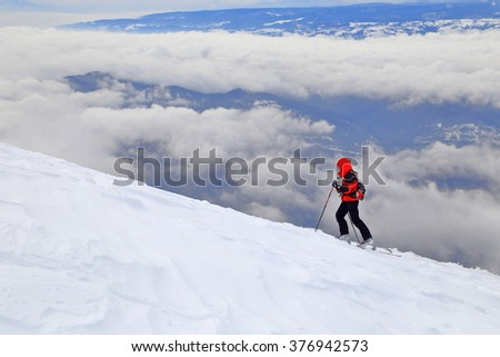 Overcast sky and mountaineer woman on touring skis above the clouds - stock photo