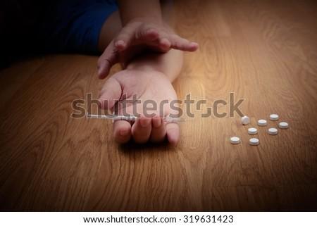 overdose male drug addict hand, drugs narcotic syringe on floor - stock photo