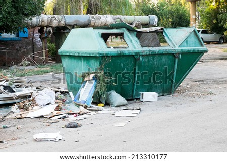 Overfilled trash dumpster in ghetto neighborhood outdoors - stock photo