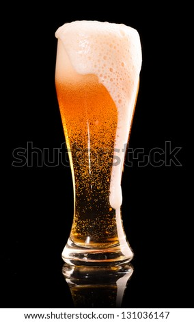 overflowed glass of fresh lager beer on black with reflection - stock photo