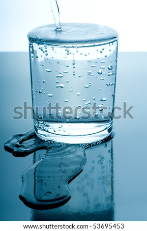 overflowed glass of water - stock photo
