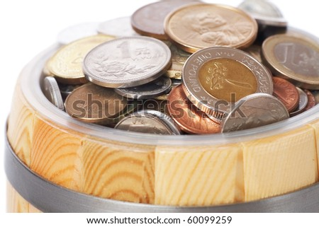 overflowing barrel with various coins - stock photo
