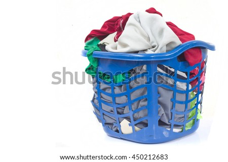 Overflowing clothes in laundry plastic basket blue on white background. - stock photo